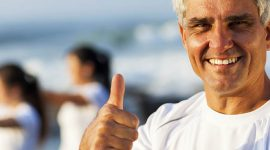 active mature man giving thumb up on beach with family exercising on background